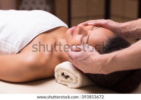 Close-up of young pretty woman relaxing during her face massage