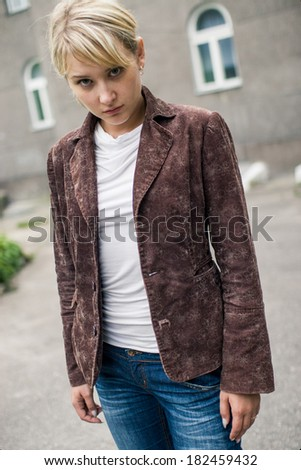 Close-up of young sad blonde girl with fringe, dressed in velvet brown jacket