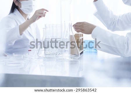 Close up of young scientists with pipette and flasks making test or research in clinical laboratory - stock photo