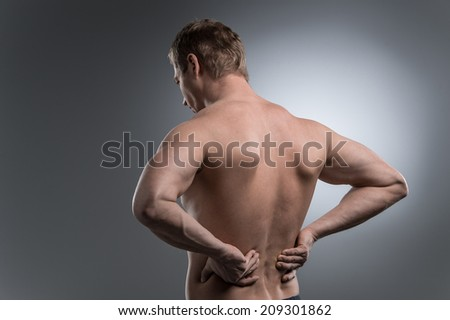 Close-up of young shirtless man with back pain. young man standing on grey white background - stock photo