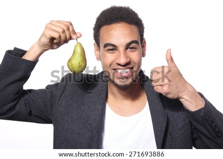 Close-up of young smiling businessman holding a pear - stock photo