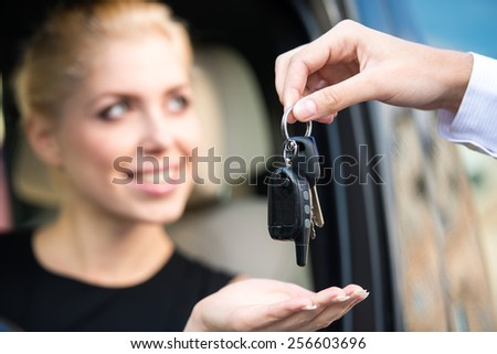 Close up of young smiling woman getting keys of a new car. Concept for car rental  - stock photo