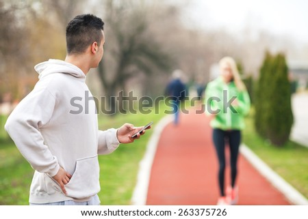 Close-up of young sport instructor looking at his student and measuring her results - stock photo