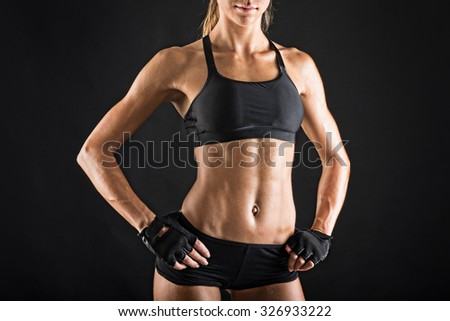 Close up of young sporty woman portrait against black background. Grunge effect.