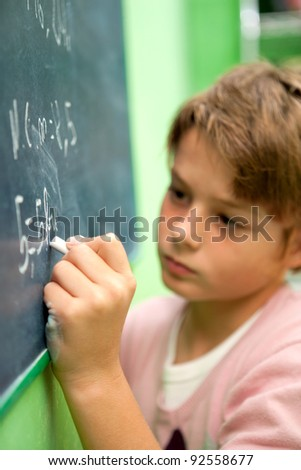 Close up of young student writing with chalk on chalkboard in classroom - stock photo