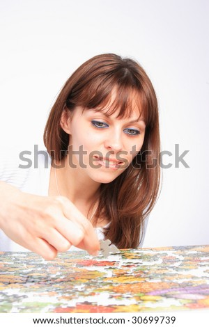 Close up of young woman doing  puzzle - stock photo