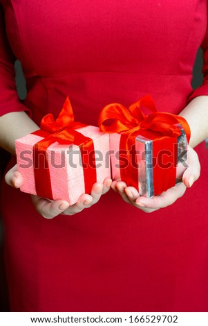 Close-up of young woman in red dress giving two presents with re - stock photo