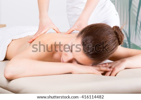 Close-up of young woman receiving back massage/ Close-up image of a young woman who laying on her stomach. She is receiving a back massage. - stock photo