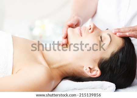 Close-up of young woman receiving facial massage at day spa - stock photo