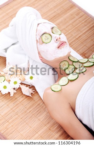Close up of Young woman relaxing with cucumber slices over her eyes