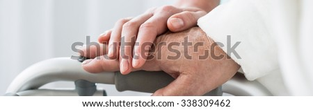Close-up of young woman's and elderly woman's hands - stock photo