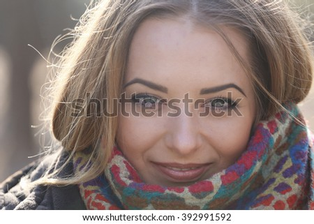 Close Up Of Young Woman's Eyes As She Smiles, Her Hair Blows In The Wind - stock photo