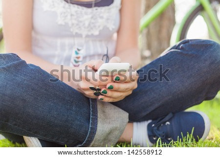Close up of young woman sitting on the grass and using smart phone.