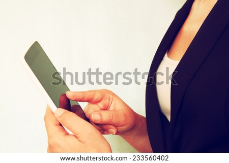 close up of young woman using tablet device. subtle retro filter - stock photo
