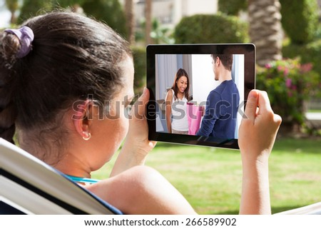 Close-up Of Young Woman Watching Movie On Digital Tablet - stock photo
