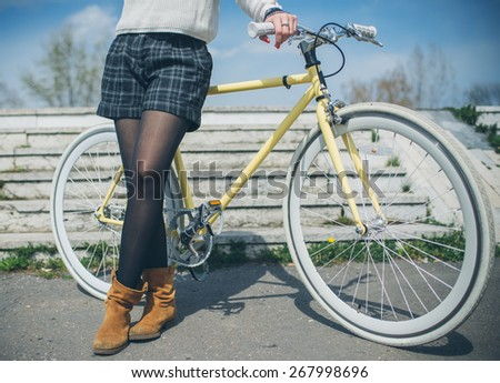 Close-up of young woman with bicycle standing outdoor - stock photo
