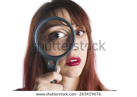 Close Up of Young Woman with Red Hair Looking Through Magnifying Glass in front of Eye, Searching for Clues - stock photo