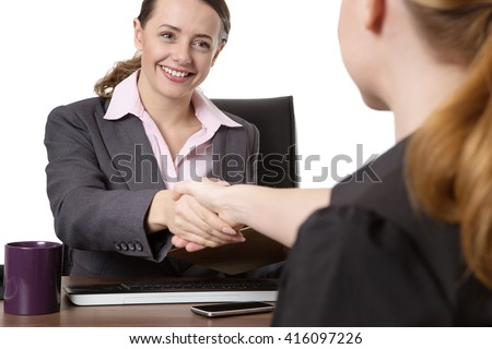 Close up office shot of two women shaking hands whilst sitting down at a desk. - stock photo