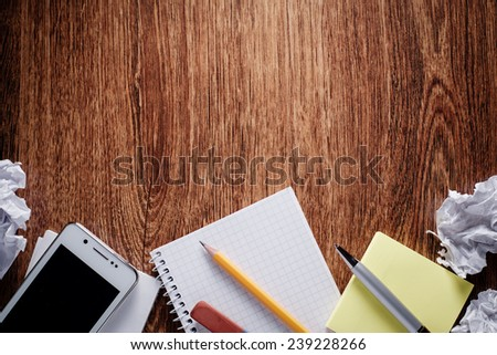 Close up Office Supplies - Phone, Notes, Pen, Pencil, Eraser and Crumpled Papers - on Wooden Table. Captured at the Bottom Border Frame with Copy Space on Top. - stock photo