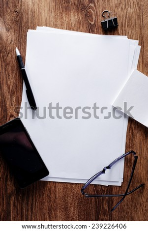 Close up Office Supplies with Mobile Phone and Eyeglasses on Wooden Table, Emphasizing Copy Space at the Center. - stock photo