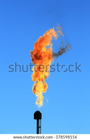 close-up oil burning torch against the blue sky