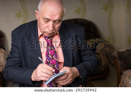 Close up Old Bald Businessman in Formal Wear, Writing Something on his Small Notes with Sad Facial Expression - stock photo