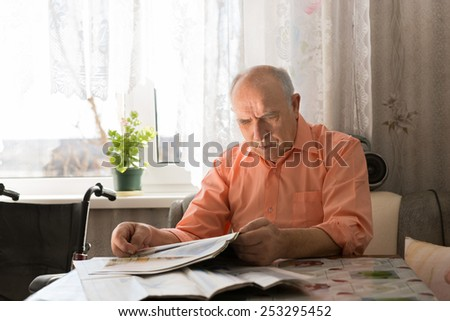 Close up Old Bald Man Reading News Updates on Tabloid While Sitting at the Living Room Near the Window. - stock photo
