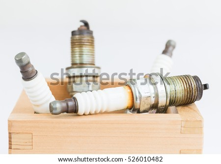 Close up old burned spark plug in wood box on white background
