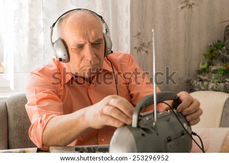 Close up Old Man Listening News Program at the Radio with Headset While Sitting at the Living Area. - stock photo