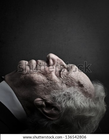 close-up old man lying down with eyes closed - stock photo