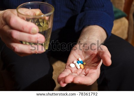 close-up old man's hands with pills and glass of water, he is going to take some medicine - stock photo