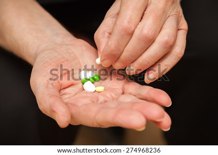 close-up old man's hands with pills, he is taking one of them - stock photo