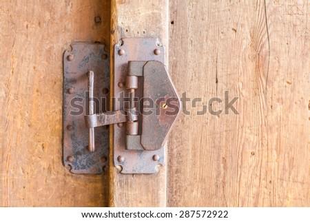 Close - up Old metal padlock and wood door - stock photo