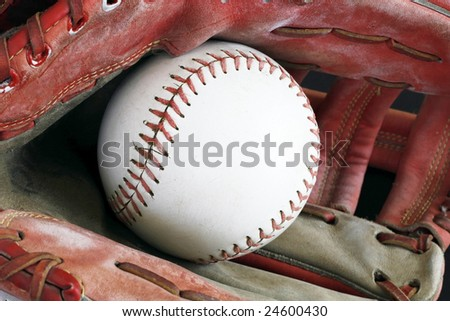 close up old red baseball mitt with baseball inside