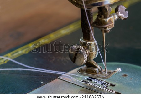 Close up old sewing machine and needle.