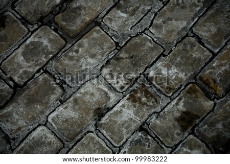 Close-up old weathered cobble stone background. - stock photo