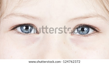 Close up on a beautiful blue eyes of a young girl - stock photo
