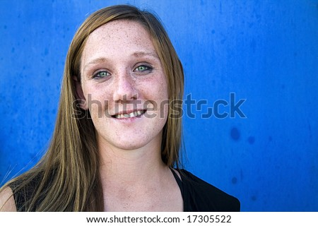 Close up on a Beautiful Girl with Blue Wall as a Background - stock photo