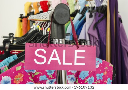 Close up on a big sale sign for summer clothes. Clearance rack with colorful summer outfits and accessories displayed on hangers. - stock photo