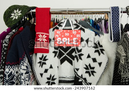 Close up on a big sale sign for winter clothes. Clearance rack with colorful winter outfits and accessories displayed on hangers. - stock photo
