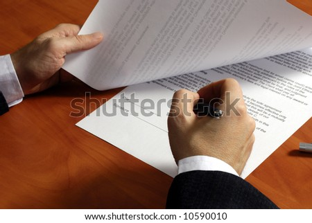close up on a businessman hands signing a contract - stock photo