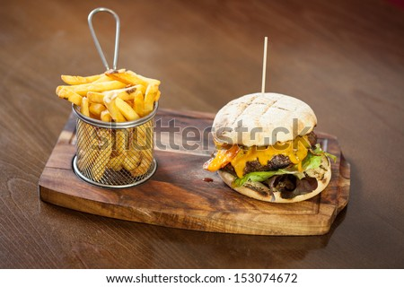 Close up on a cheese burger and french fries served in classy restaurant on a wooden board - stock photo