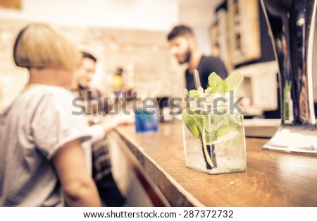 close up on a cocktail in a bar. barman and customers are standing in the back. concept about bar, profession and people. - stock photo