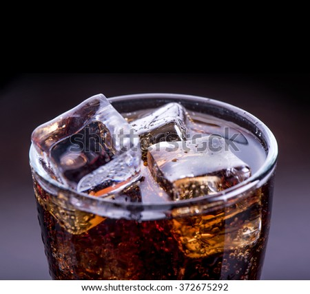 Close up on a cold refreshing soft drink with ice on a black background