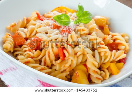Close up on a dish of fresh pasta with tomato, pepper and cheese