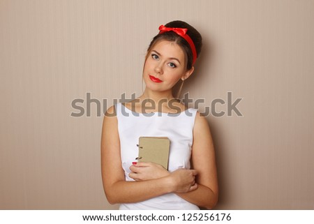 Close-up on a green background attractive girl a little book