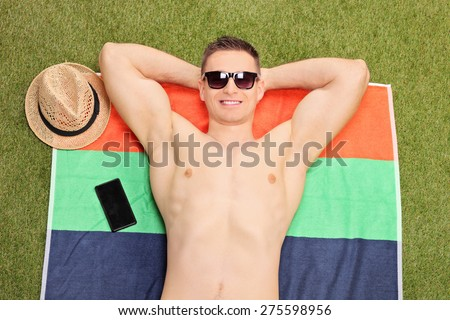 Close-up on a handsome young man lying on a towel and sunbathing in his backyard - stock photo