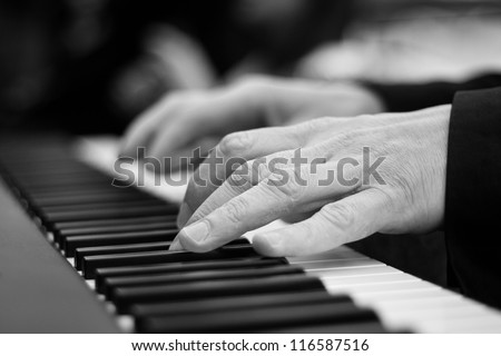 Close-up on a man's hand playing the piano - stock photo