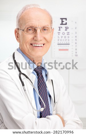 Close up on a mature optician posing in his office with an eyesight test in the background - stock photo