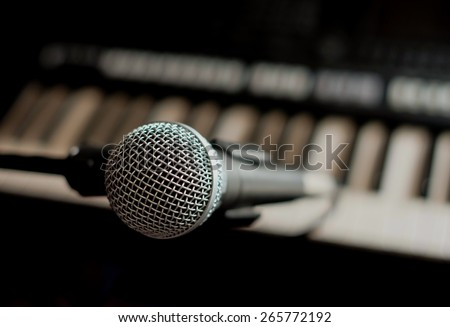 Close up on a microphone during recording session with a singer, piano in the background - stock photo